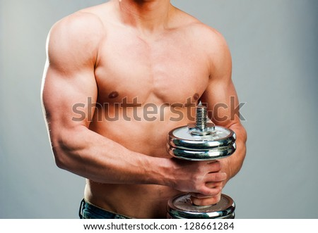 Torso of handsome muscular man use his dumbbell to exercise - stock photo