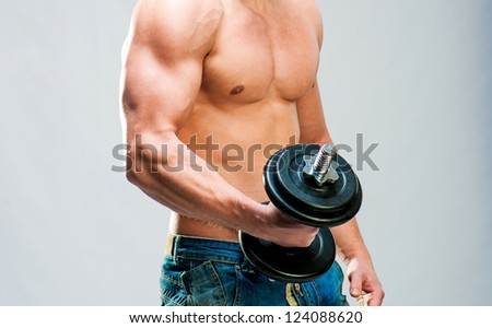 Torso of muscular man with weights on a gray background - stock photo