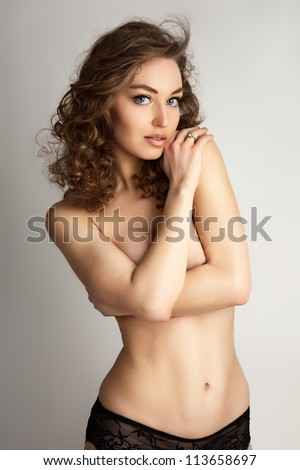 Torso of naked female keeping her arms on breasts over grey background.