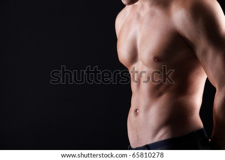 Torso of strong man in jeans against dark background - stock photo