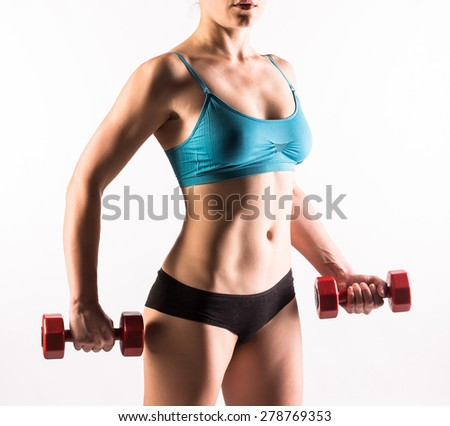 Torso of young fit woman with dumbbells on white background