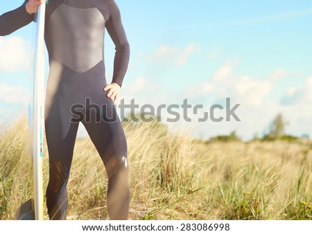 Torso view of a fit muscular surfer wearing a wetsuit balancing his board upright standing amongst coastal grasses on top of a sand-dune, with copyspace - stock photo