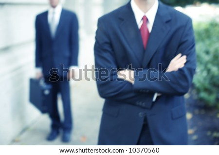 torso view of two businessmen standing in front of building with arms folded - stock photo