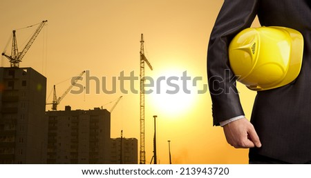 torso worker or engineer holding yellow helmet for workers security on background of new highrise apartment buildings and construction cranes on background of sunset sky Silhouette Crane lifts load - stock photo