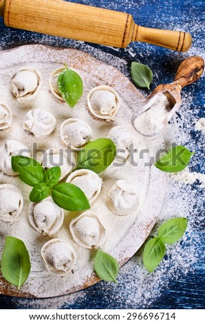 Tortelli raw, sprinkled with flour, Basil leaves on a wooden surface - stock photo