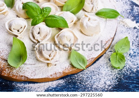 Tortelli raw, sprinkled with flour, Basil leaves on a wooden surface