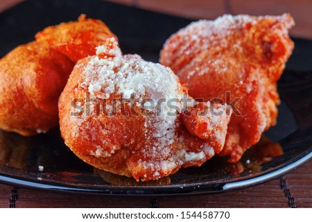 Tortelli, typical Carnival Italian dessert, covered by sugarover black plate - stock photo