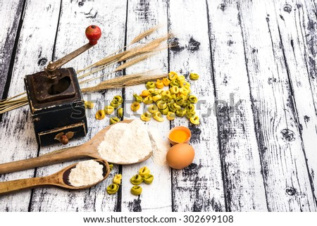 tortellini and other products on textured wooden table - stock photo