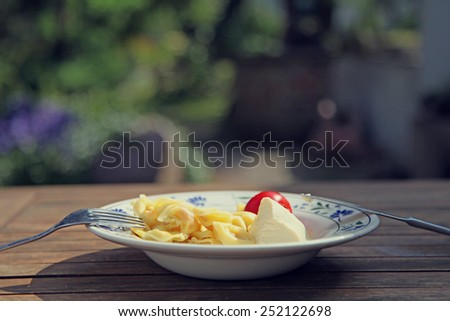 Tortellini and tomatos on plate outdoors in sunlight - stock photo