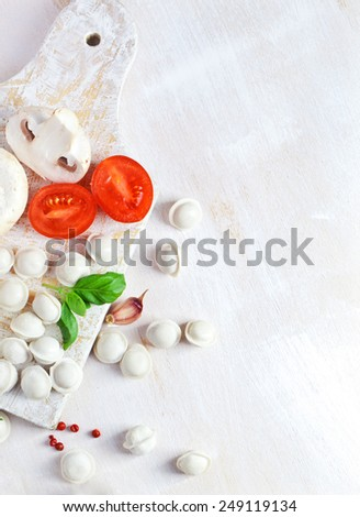 Tortellini and vegetables on white wooden background - stock photo