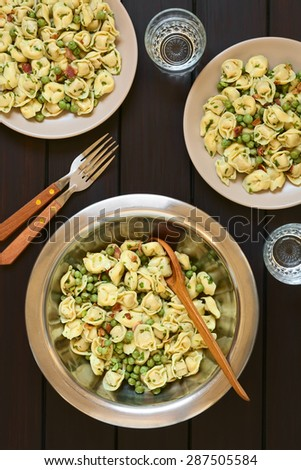 Tortellini salad with green peas, fried bacon and parsley in big salad bowl with spoon to serve, salad served on two plates, forks and glasses, photographed overhead on dark wood with natural light - stock photo