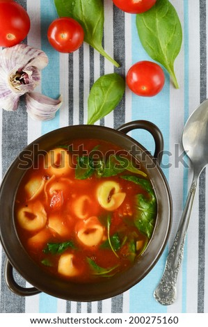tortellini soup with tomato, spinach, bazil and garlic - stock photo