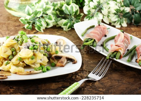 Tortellini with cream, mushrooms and peas on complex background - stock photo