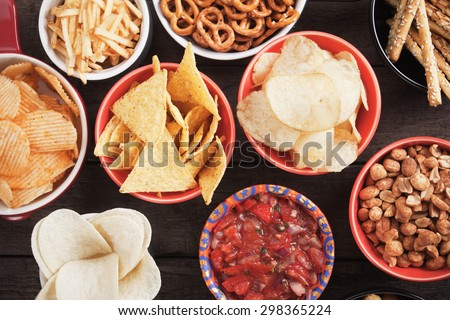 Tortilla chips and other salty snacks with homemade salsa - stock photo