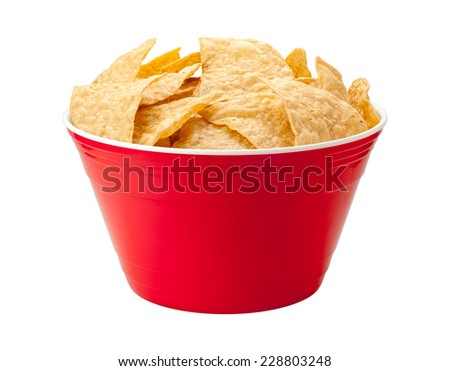 Tortilla chips in a red plastic party bow isolated on white. A salty snack associated with parties, and watching sporting events, often served with salsa dip.  - stock photo