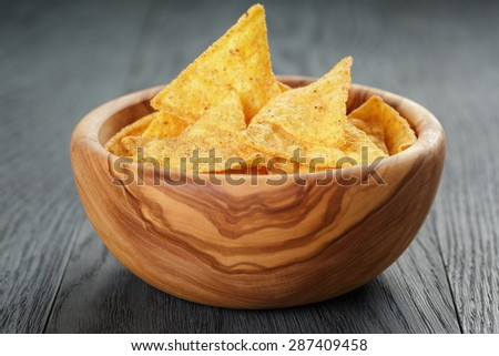 tortilla chips in olive wood bowl on wooden table, selective focus - stock photo