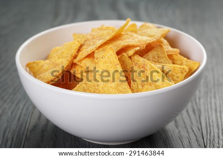 tortilla chips in white bowl on wooden table, selective focus - stock photo