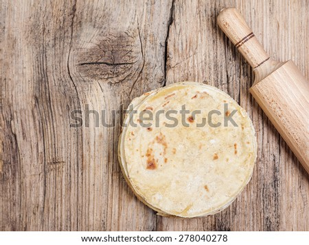 tortilla chips on textured wooden table with wooden rolling pin - stock photo