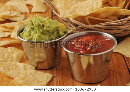 Tortilla chips with servings of salsa and guacamole on a wooden surface