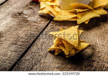 Tortilla chips with tomato and cheese-garlic dip on wood old table - stock photo