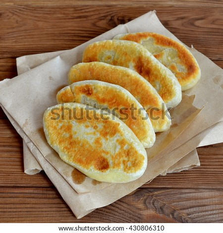 Tortilla dough stuffed with cheese on a paper and wooden background. Fried pies closeup. Easy delicious food recipe. Tasty snack idea. Homemade yummy fried pies with filling - stock photo