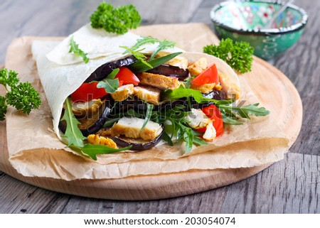 Tortilla filled with grilled chicken, aubergine, tomato and rocket - stock photo