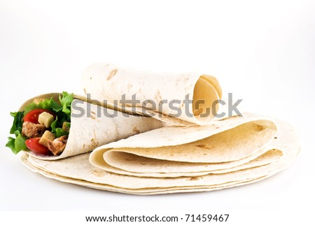 Tortilla filled with lettuce chicken tomatoes and cucumber with plain tortillas - stock photo