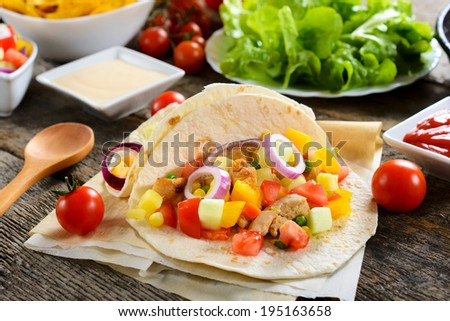Tortilla sandwiches with chicken meat and vegetables.Selective focus on the front tortilla  - stock photo