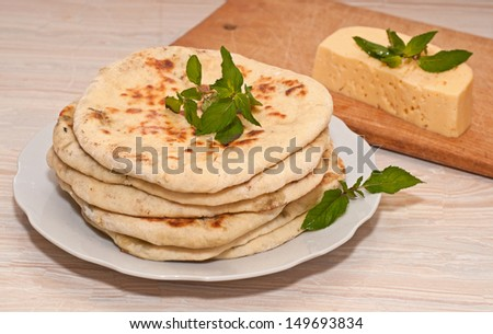 tortilla with cheese and mint on white plate - stock photo