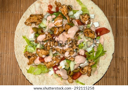 Tortilla with grilled chicken and vegetables on bamboo mat background - stock photo