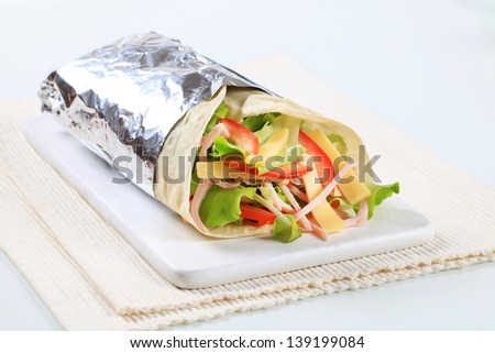 Tortilla wrap with cheese and fresh salad on a cutting board - stock photo