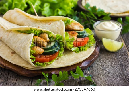tortilla wrap with chicken and vegetables, selective focus - stock photo