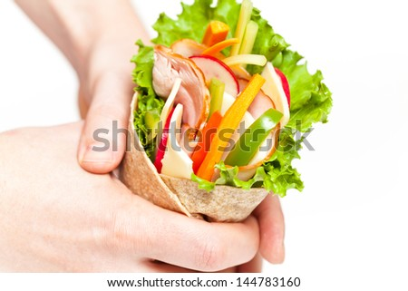 Tortilla Wrap with meat in hand on white - stock photo