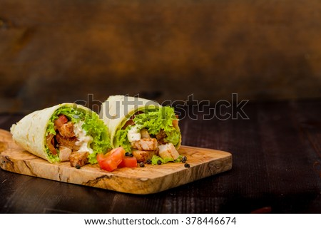Tortilla wraps with fresh ingredients on a wooden background - stock photo