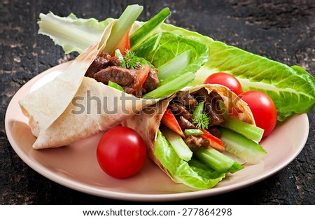 Tortilla wraps with meat and fresh vegetables - stock photo