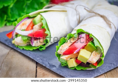 Tortilla wraps with roasted chicken fillet, avocado, tomato, onion and puprika - stock photo