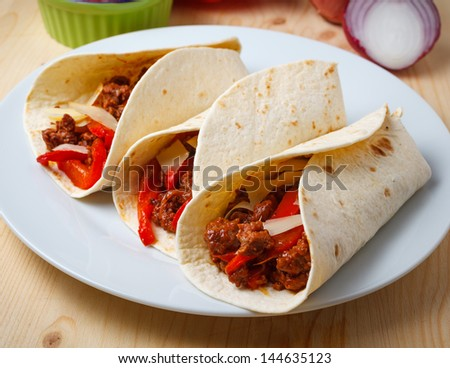 tortillas filled with  with beef meat, pepperoni, onions, cheese and tomato sauce