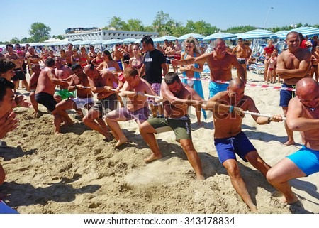 Tortoreto (TE), Italy - 2013, August: Team of men in swimsuit competing in a tug of war on the beach