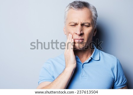 Torturing pain. Frustrated senior man in T-shirt holding hand on his cheek while standing against grey background - stock photo
