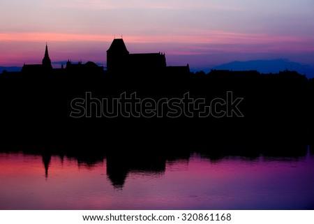 Torun Old City skyline at twilight in Poland, reflection on Vistula river waters. - stock photo