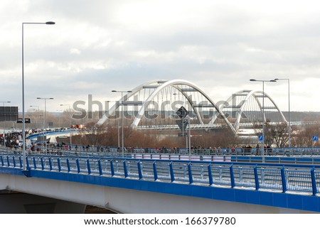 TORUN, POLAND - DECEMBER 07, 2013: opening of a new arch bridge over the Vistula River. The bridge - co-financed by European Union - consists of two 270 m long spans, that are the longest in Poland. - stock photo