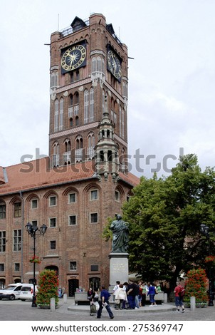 Torun, Poland - June 20, 2009: People at the monument to the astronomer Nicolaus Copernicus in front of the City hall at Rynek Staromiejski in the old town of Torun in Poland.