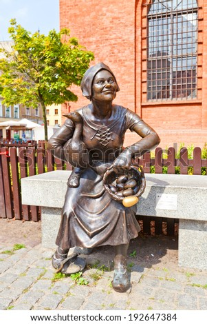 Torun, Poland - May 06, 2014: Statue of market woman on the bench. Square Rynek Nowomiejski of Torun town, Poland. UNESCO site. Work of sculptors Anety and Macieja Jagodzinskich-Jagenmeer, 2011