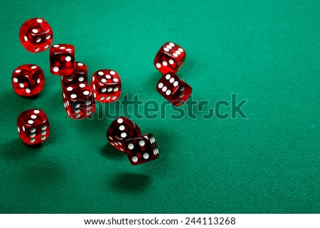 tossing transparent red dice over green felt