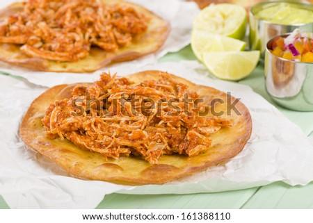 Tostadas - Mexican crispy corn tortilla topped with chicken tinga. Served with pico de gallo, guacamole and crema mexicana. - stock photo