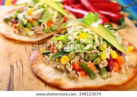 Tostadas with ground beef and vegetables on wooden background - stock photo