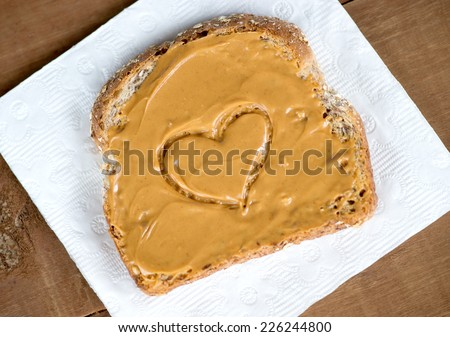 Tosted peanut butter sandwich on tissue against wooden board with heart shape - stock photo