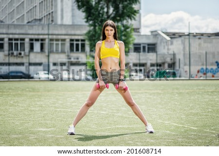 Total body workout. Fitness woman in tracksuit and dumbbell training on the football field on a hot sunny day. - stock photo