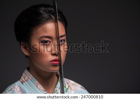 Total concentration. Young beautiful Japanese woman in kimono looking at camera and holding katana sword by her face while standing against grey background with copy space - stock photo