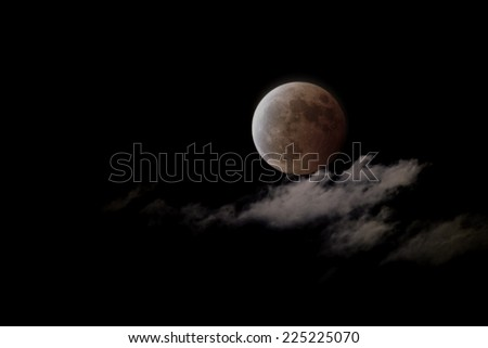 Total lunar eclipse with cloud on dark night sky. - stock photo